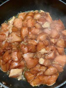 De soyamarinerede kyllingestykker brunes på panden