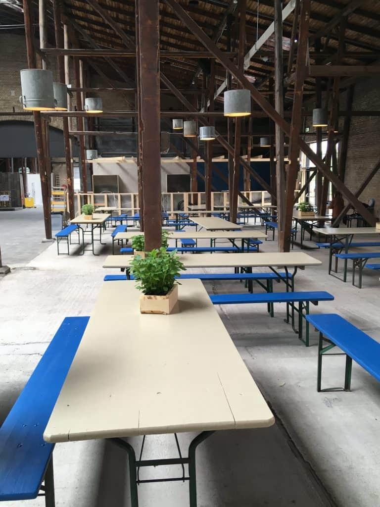 Fede lamper, blå bænke og hvide borde